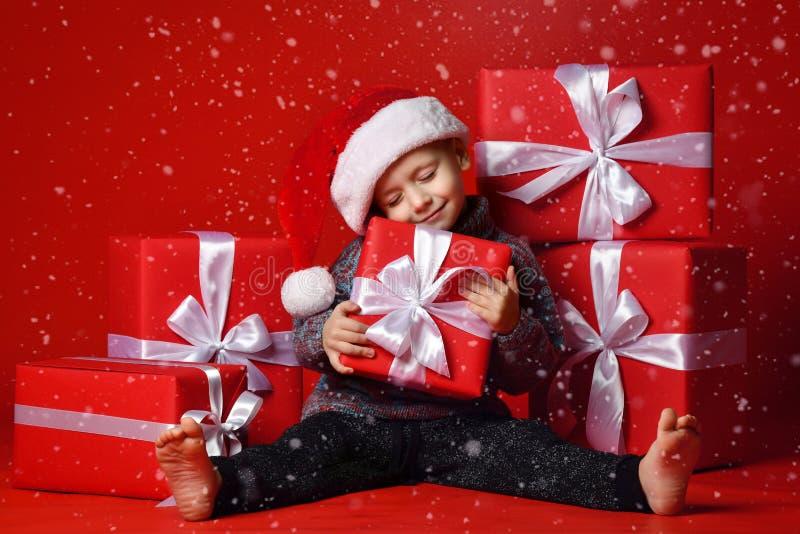 Criança engraçada de sorriso no chapéu vermelho de Santa que mantém o presente do Natal disponivel Conceito do Natal fotos de stock royalty free