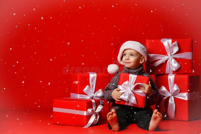 Criança engraçada de sorriso no chapéu vermelho de Santa que mantém o presente do Natal disponivel Conceito do Natal imagem de stock royalty free