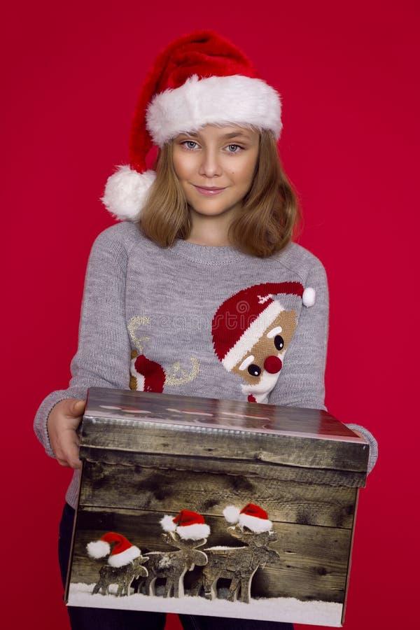 Criança engraçada de sorriso no chapéu vermelho de Santa que mantém o presente do Natal disponivel Conceito do Natal imagem de stock