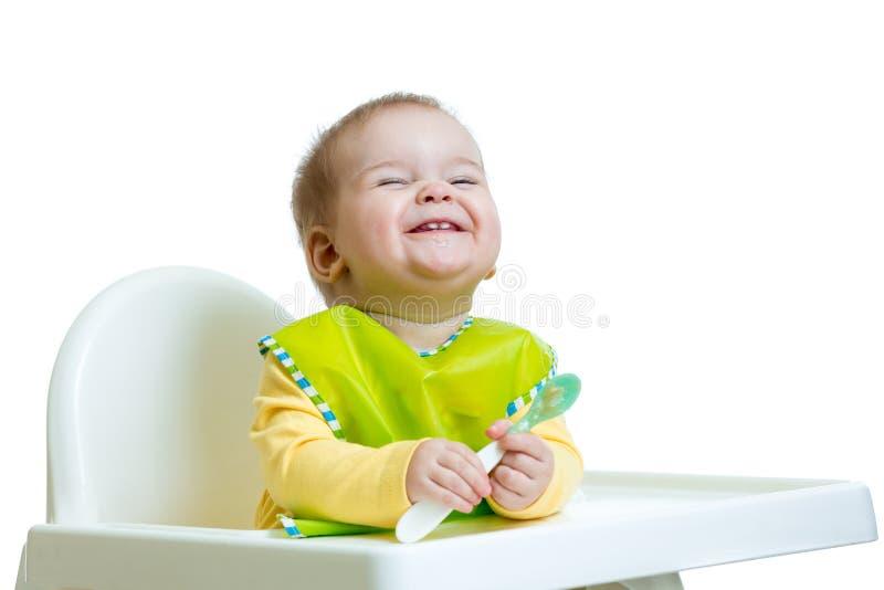Criança engraçada do bebê que senta-se no cadeirão com uma colher fotografia de stock royalty free