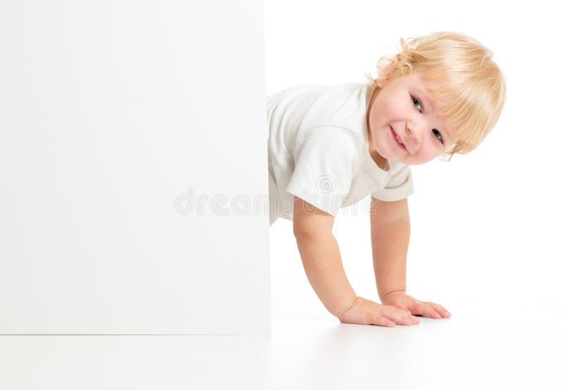 Criança engraçada em todos os fours atrás da bandeira foto de stock royalty free