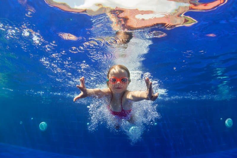 A criança engraçada nos óculos de proteção mergulha na piscina imagens de stock royalty free