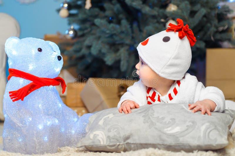 A criança engraçada olha um urso Natal Ano novo fotos de stock royalty free