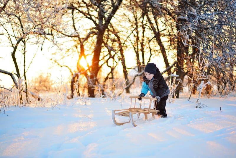 Criança engraçada pequena bonito na roupa do inverno que tem o divertimento com neve, fora durante a queda de neve Crianças ativa fotos de stock
