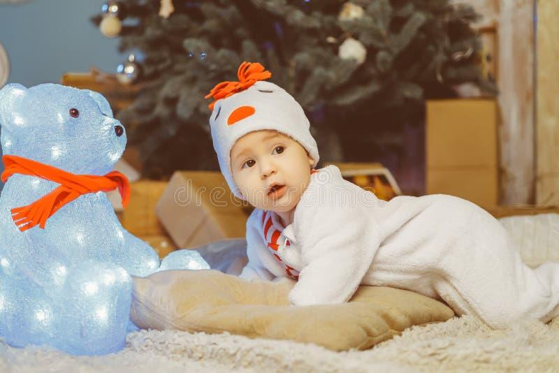 Criança engraçada que encontra-se na cama ao lado do urso de peluche foto de stock