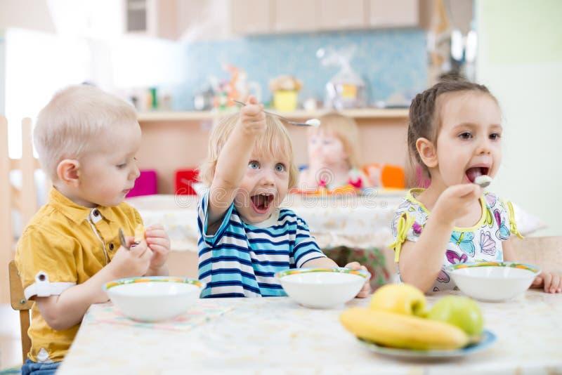 Criança engraçada que joga e que come no jardim de infância foto de stock