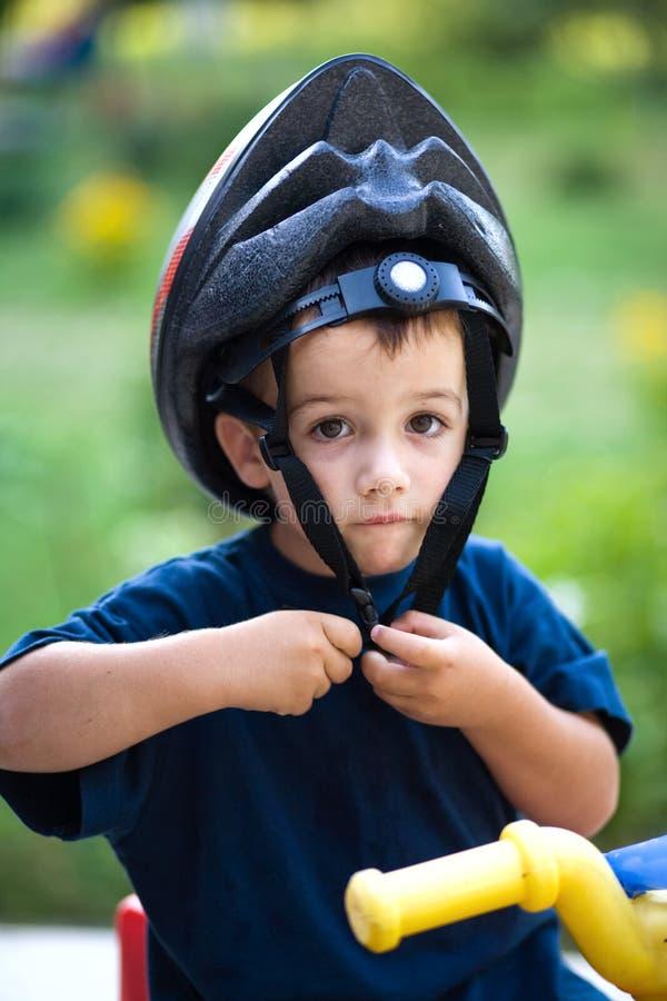Criança engraçada que põr o capacete fotografia de stock