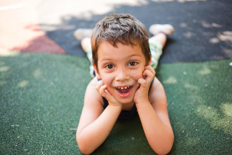 Criança engraçada que senta-se na terra imagem de stock