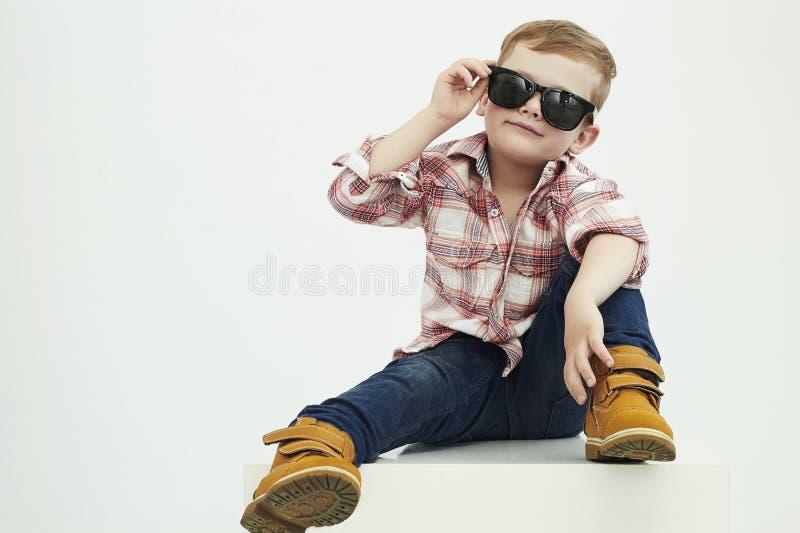 Criança engraçada Rapaz pequeno elegante nos óculos de sol criança à moda em sapatas amarelas imagens de stock royalty free