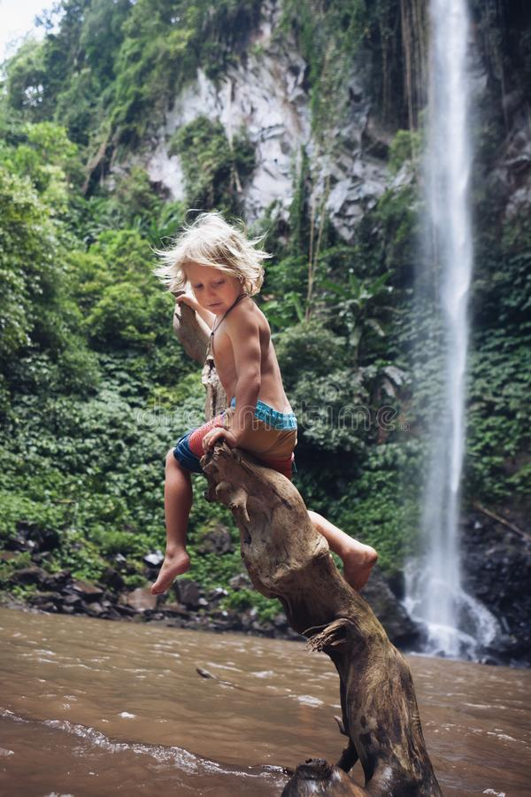 A criança engraçada senta-se na senão sob a cachoeira na selva tropical fotografia de stock royalty free