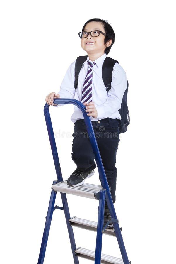 A criança escala acima uma escada imagem de stock royalty free