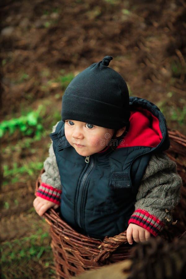 A criança escalou na cesta feito a mão fotos de stock