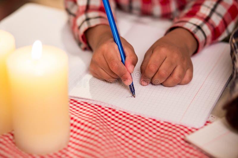 A criança escreve a letra pela luz de vela imagem de stock royalty free
