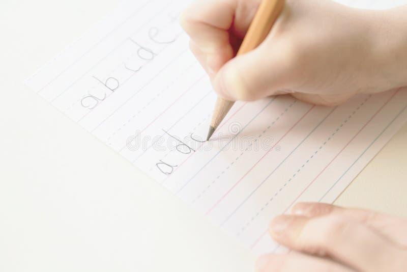 A criança escreve o alfabeto com lápis mas mistura acima b e d; fotos de stock