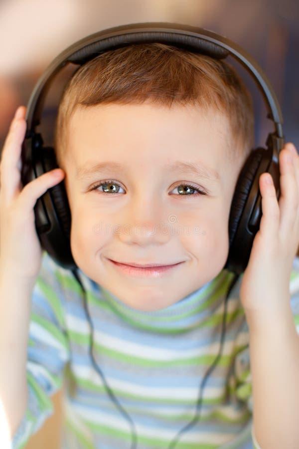 A criança escuta a música através dos fones de ouvido foto de stock