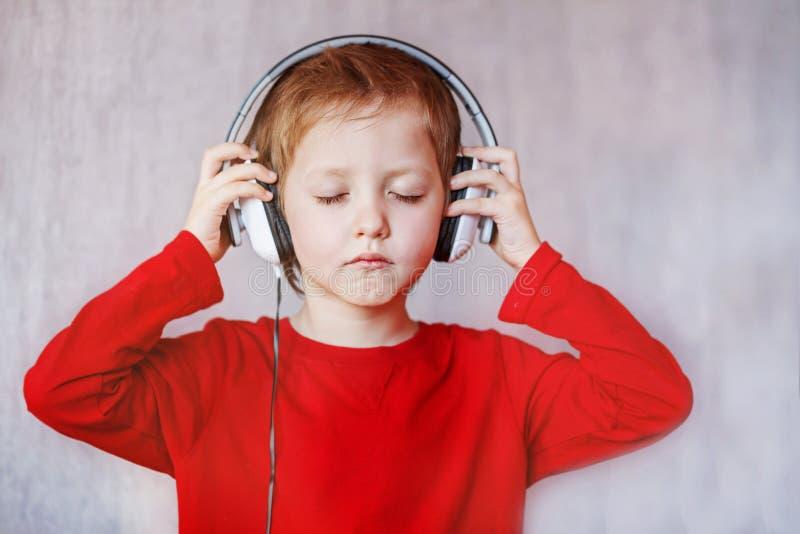 A criança escuta música em casa Criança com fones de ouvido imagens de stock