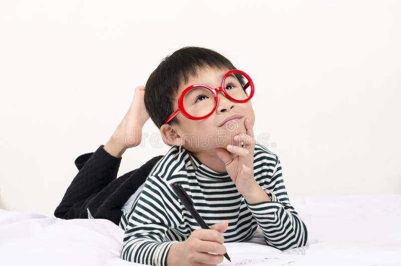 Criança esperta que encontra-se na cama imagens de stock