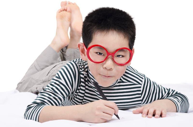 Criança esperta que encontra-se na escrita e no pensamento da cama foto de stock