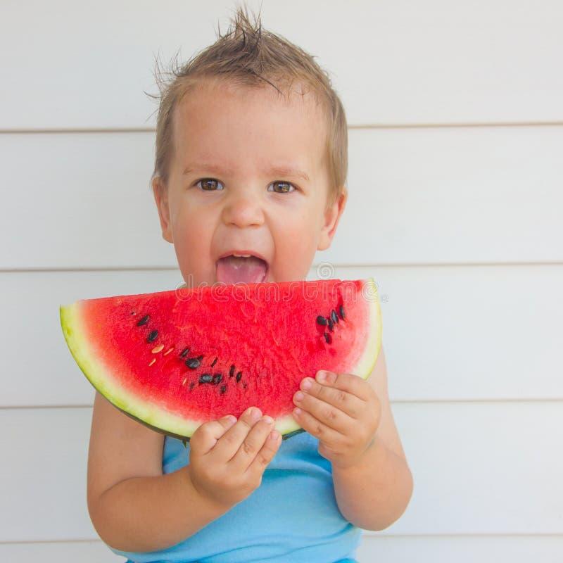 A criança está comendo uma melancia verão, um menino fotografia de stock royalty free