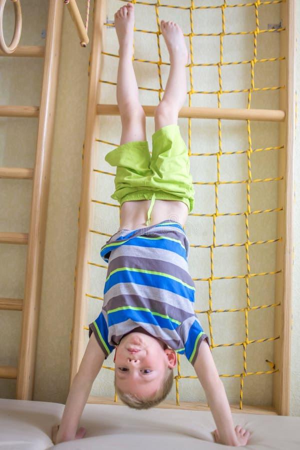 A criança está de cabeça para baixo no gym fotografia de stock