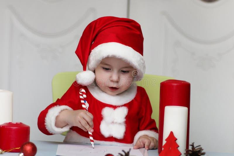 A criança está escrevendo a letra a Santa fotos de stock