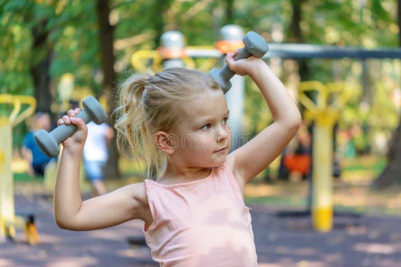A criança está fazendo o exercício com pesos Uma menina com cabelo louro Jogando esportes foto de stock royalty free