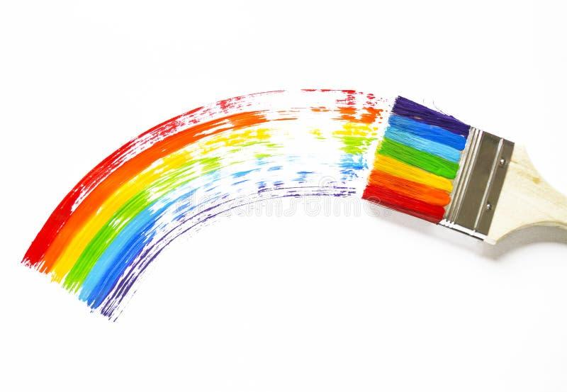 A criança está guardando a escova A criança pinta uma folha de bordo pintada em todas as cores do arco-íris Arco colorido fotos de stock