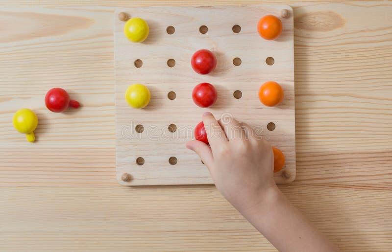 A criança está jogando com as bolas coloridas de madeira Jogo para crianças imagem de stock