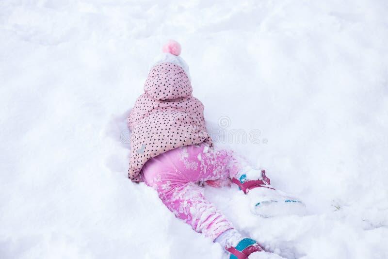 A criança está jogando na neve fotografia de stock royalty free
