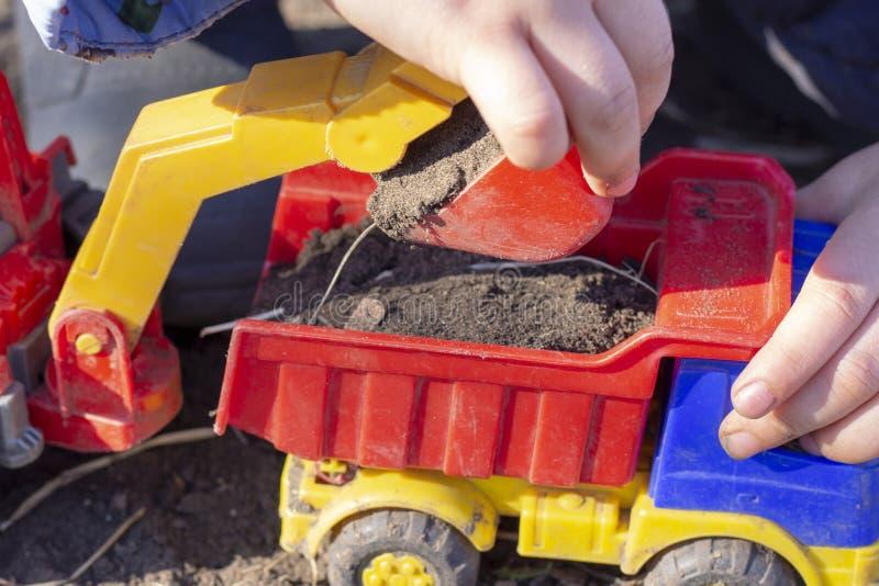 A criança está jogando na rua com areia; carrega a terra em um brinquedo do caminhão basculante fotos de stock