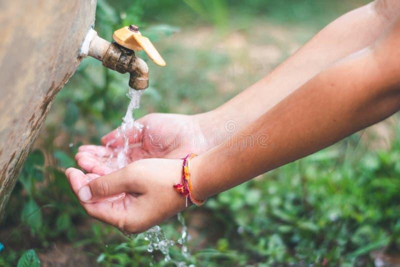 A criança está lavando suas mãos do torneira fotografia de stock royalty free