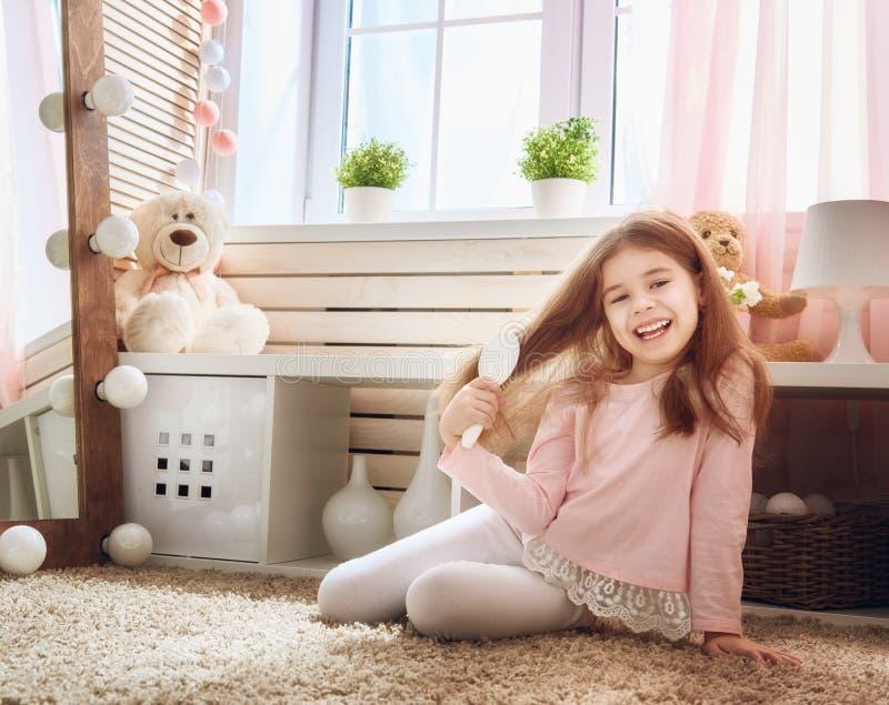 A criança está penteando perto do espelho imagem de stock