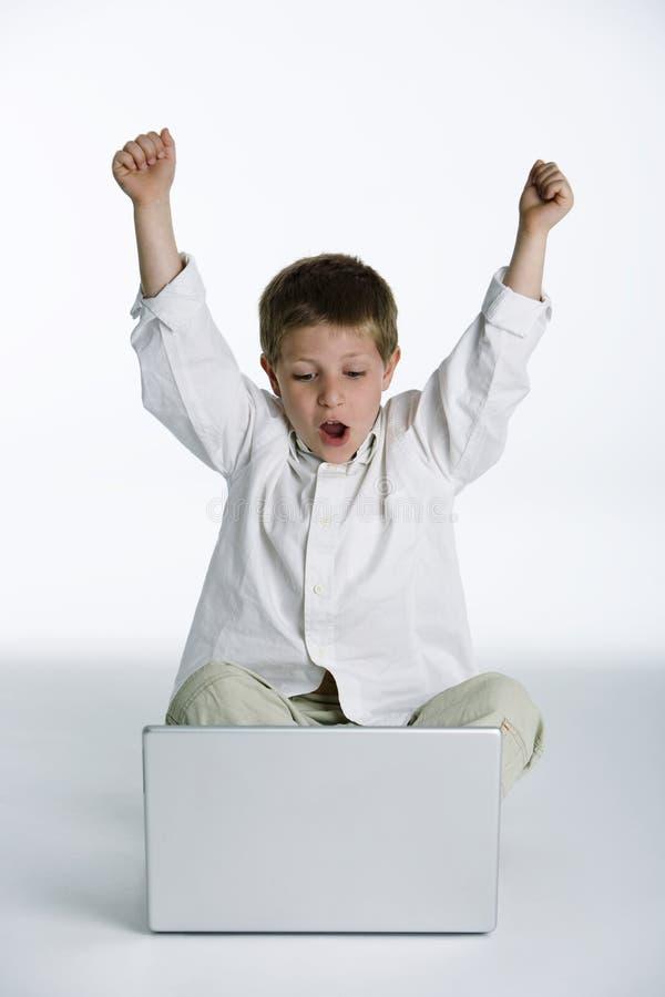Criança excitada com computador portátil imagem de stock