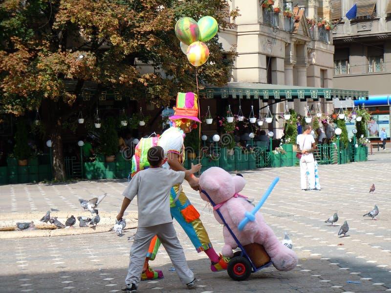 A criança exige para balões Palhaço Quadrado central fotos de stock