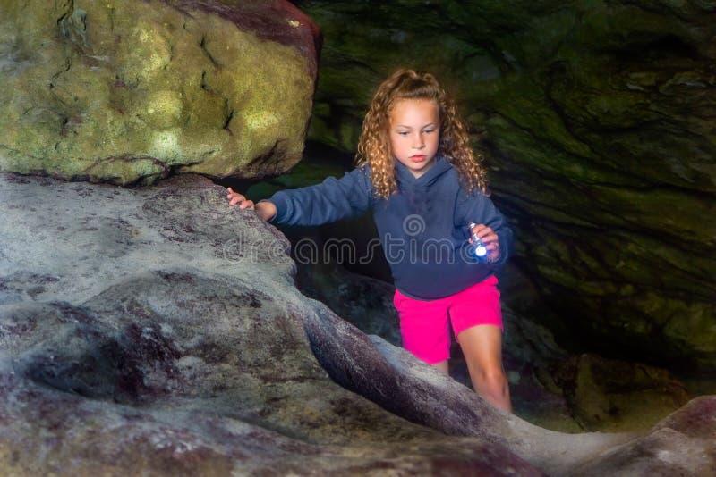 A criança explora a caverna fotografia de stock