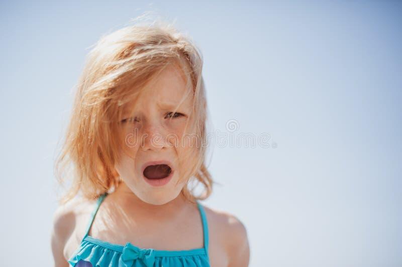 A criança expressa o descontentamento com gritos e emoções fotografia de stock