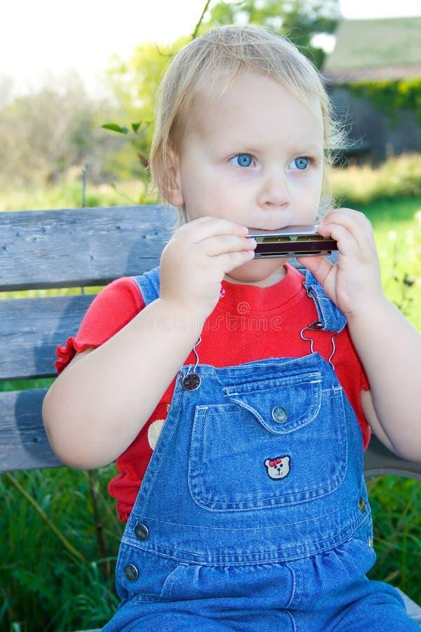 Criança eyed azul que joga a harmônica. fotos de stock royalty free