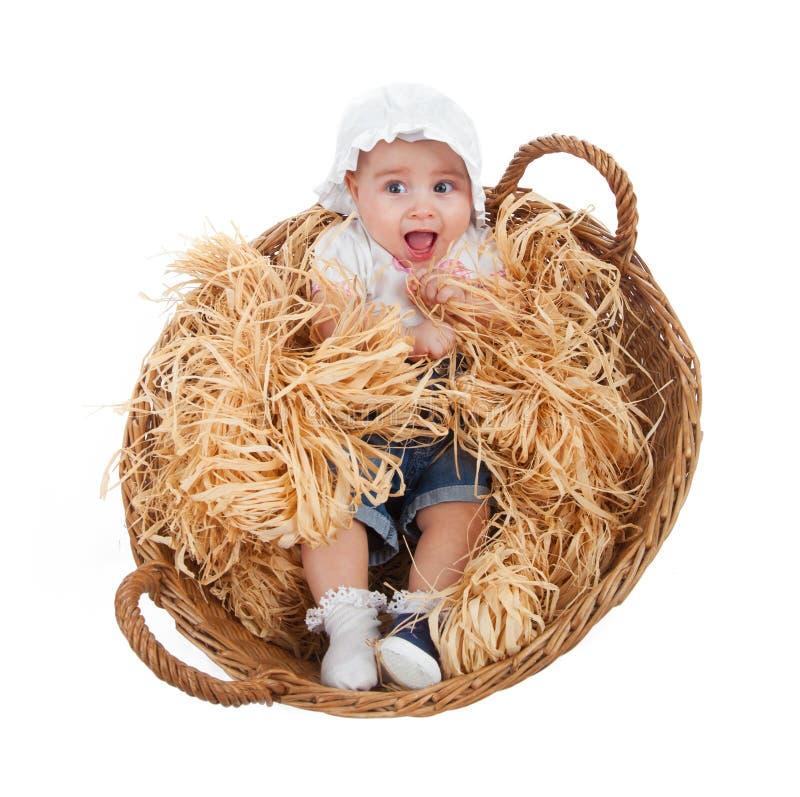Criança fêmea bonito em uma cesta da palha fotografia de stock