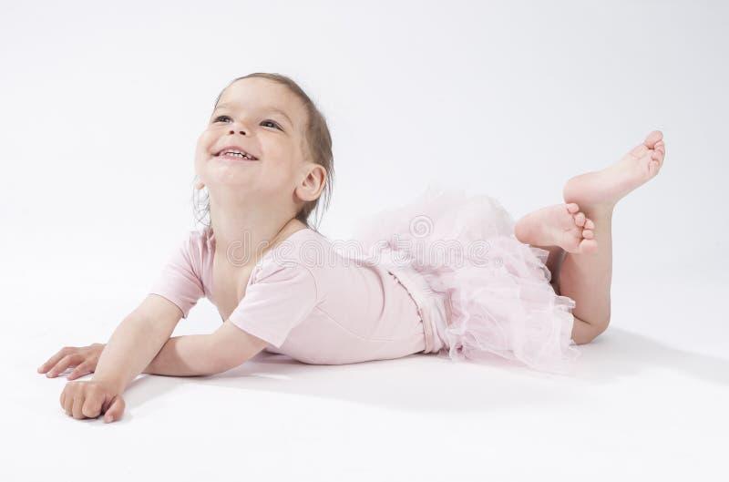 Criança fêmea caucasiano de sorriso feliz que coloca no assoalho contra o branco foto de stock royalty free
