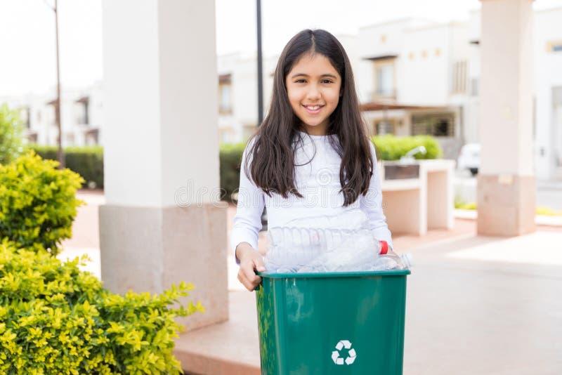 Criança fêmea com o escaninho de reciclagem com garrafas plásticas fotografia de stock royalty free