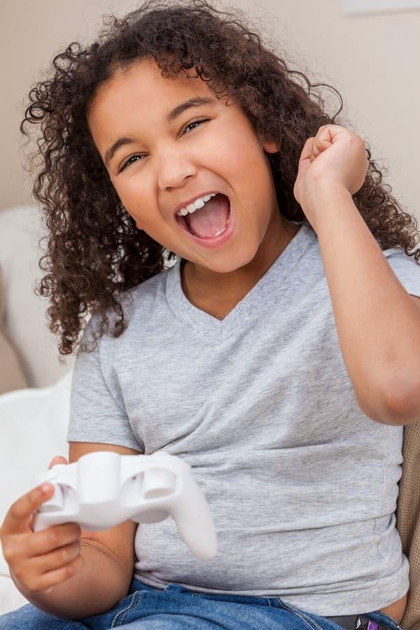 Criança fêmea da menina afro-americano Biracial que joga jogos de vídeo fotos de stock royalty free