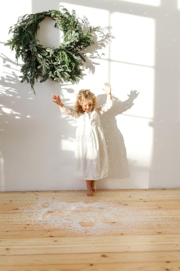 Criança fêmea loura pequena brincalhão no vestido branco, neve artificial dos lances no ar, poses na sala acolhedor branca com si fotografia de stock