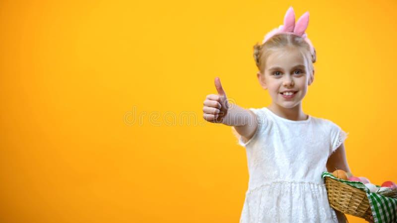 Criança fêmea na cesta da Páscoa da terra arrendada da faixa das orelhas do coelho e mostrar nos polegares acima imagens de stock royalty free