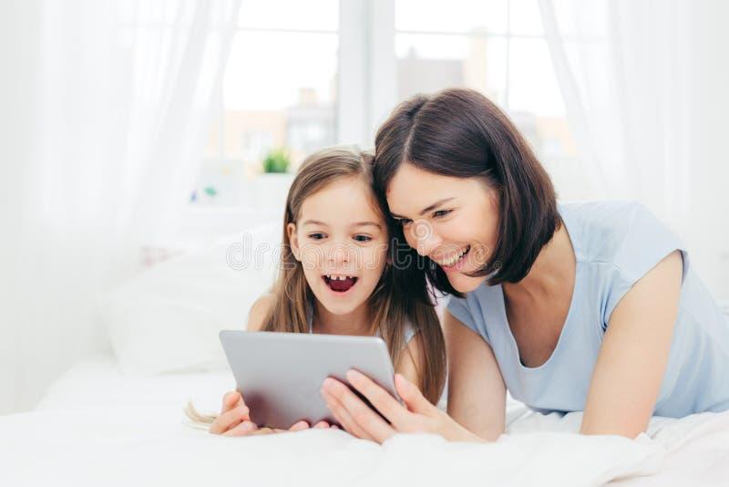 Criança fêmea pequena alegre positiva e seus desenhos animados interessantes do relógio novo da mãe na tabuleta, conectada ao Int foto de stock