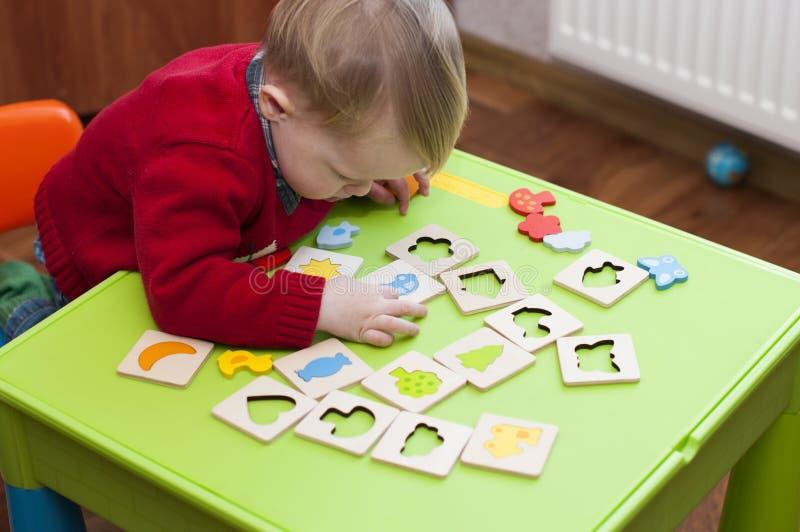 Criança fascinada pelo jogo do classificador de madeira imagem de stock