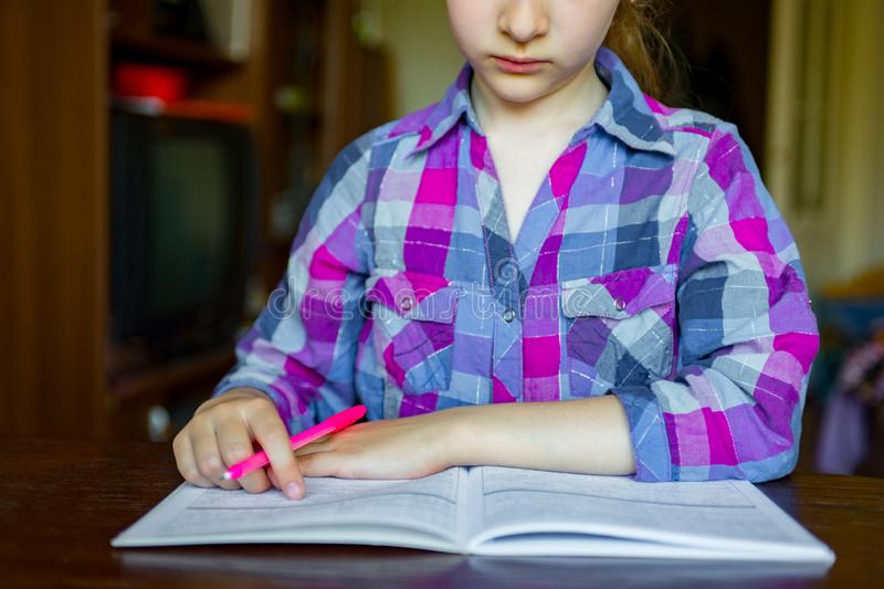 A criança faz seus trabalhos de casa Caderno para matemático Pena da posse da mão Aprendizagem da menina fotos de stock