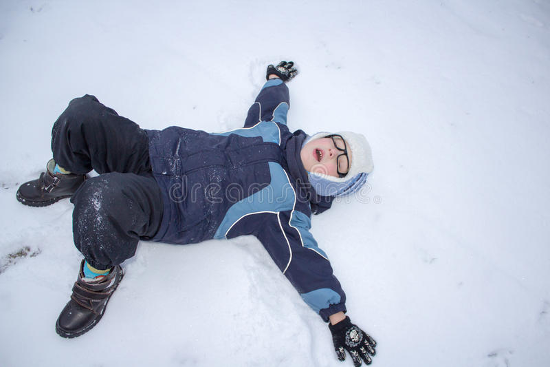 A criança faz um anjo da neve imagens de stock