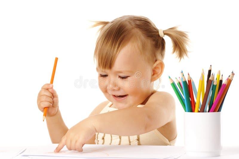 A criança feliz aponta em seus desenho e sorriso fotografia de stock