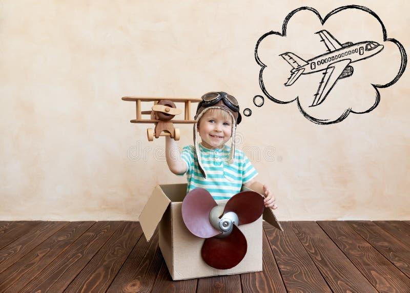 Criança feliz brincando com avião de brinquedo fotografia de stock royalty free