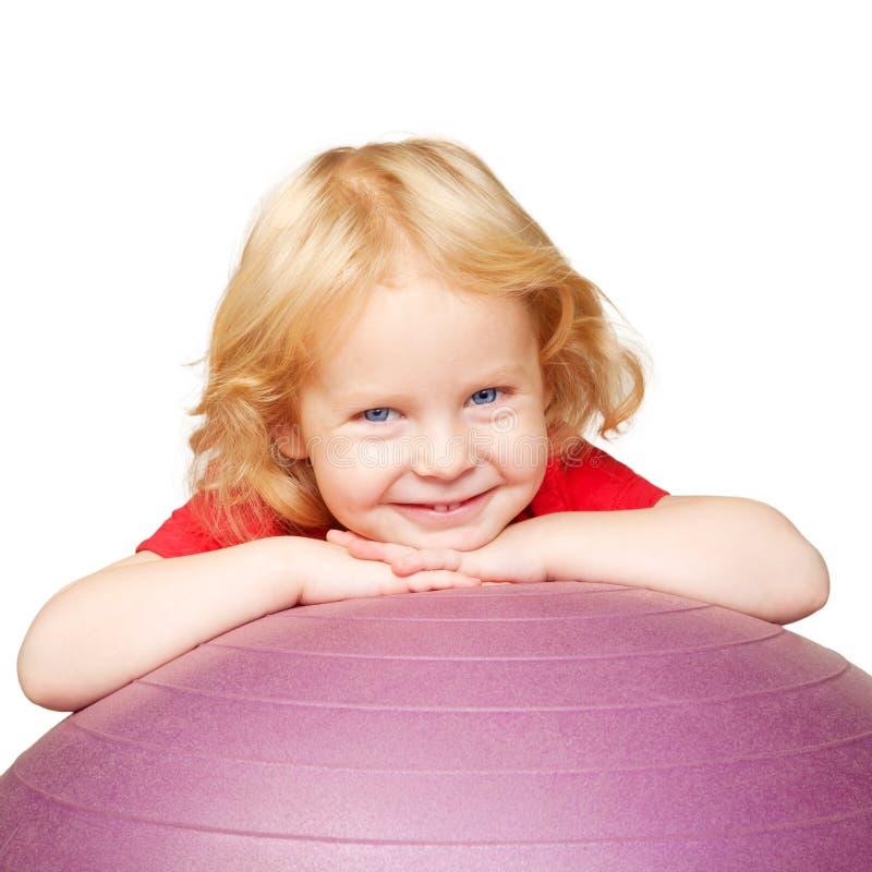 Criança feliz com a bola da aptidão que joga esportes. fotos de stock